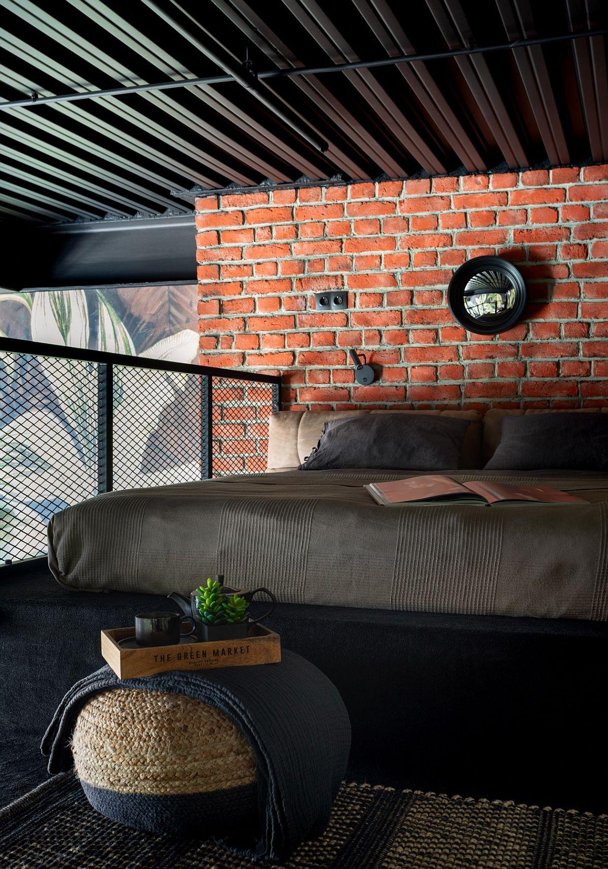 Tường gạch và lưới kim loại thông minh mang lại sự tương phản kết cấu phong phú cho phòng ngủ công nghiệp nhỏ này