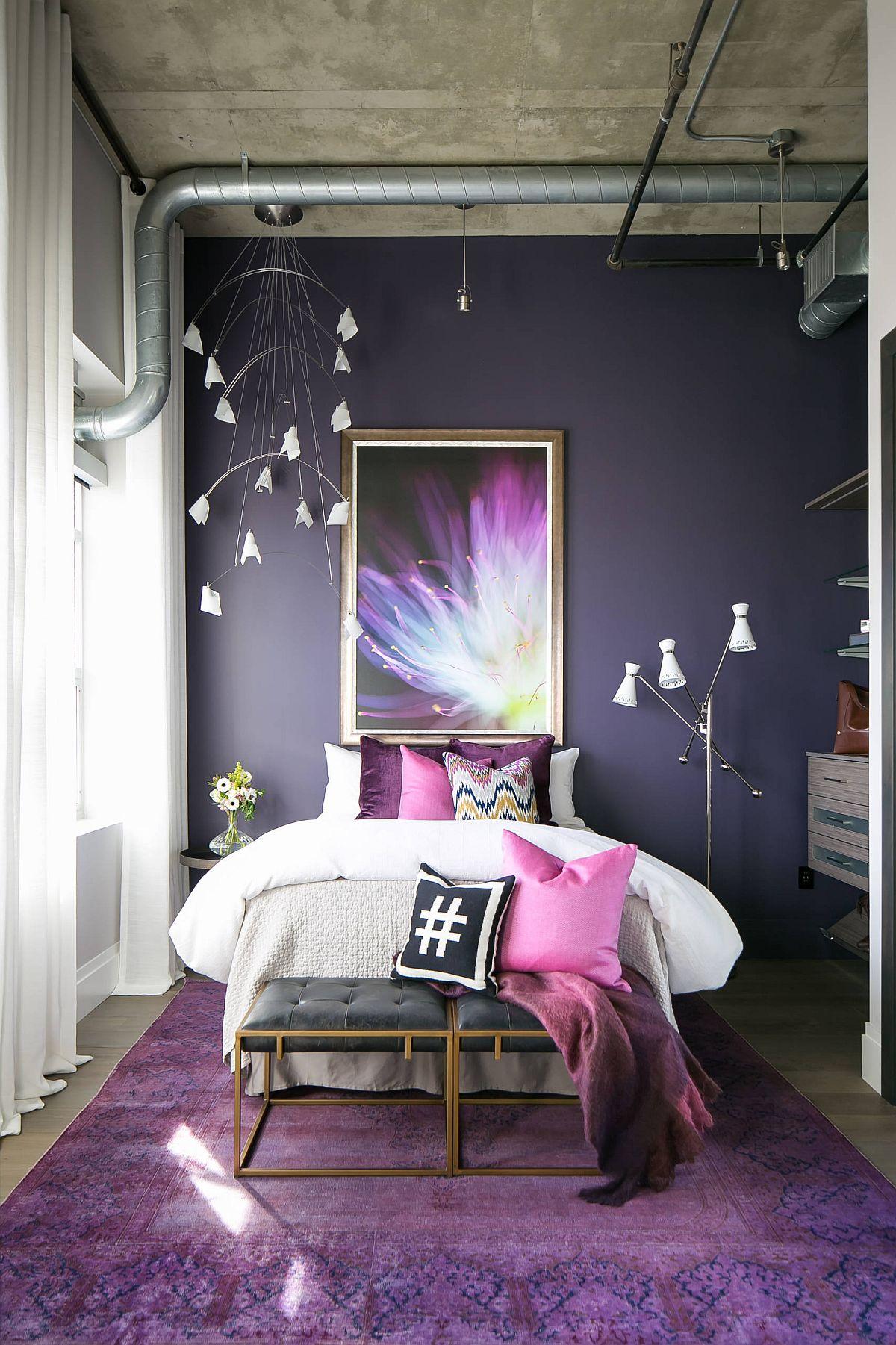 Trần bê tông và các đường ống dẫn lộ ra ngoài mang lại vẻ đẹp công nghiệp cho phòng ngủ đầy màu sắc tím này