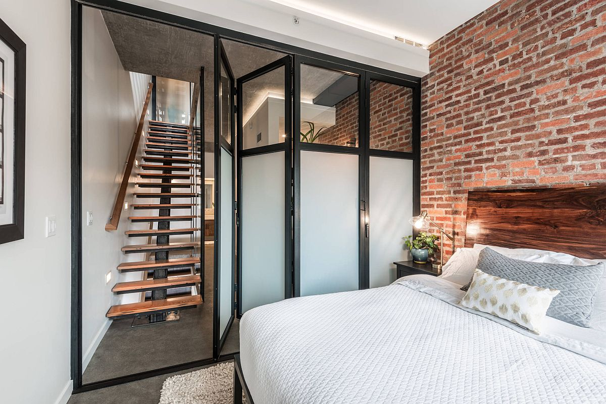 Cửa gấp và phông nền trung tính làm tăng thêm thiết kế rộng rãi cho phòng ngủ công nghiệp nhỏ này với bức tường gạch nổi bật
