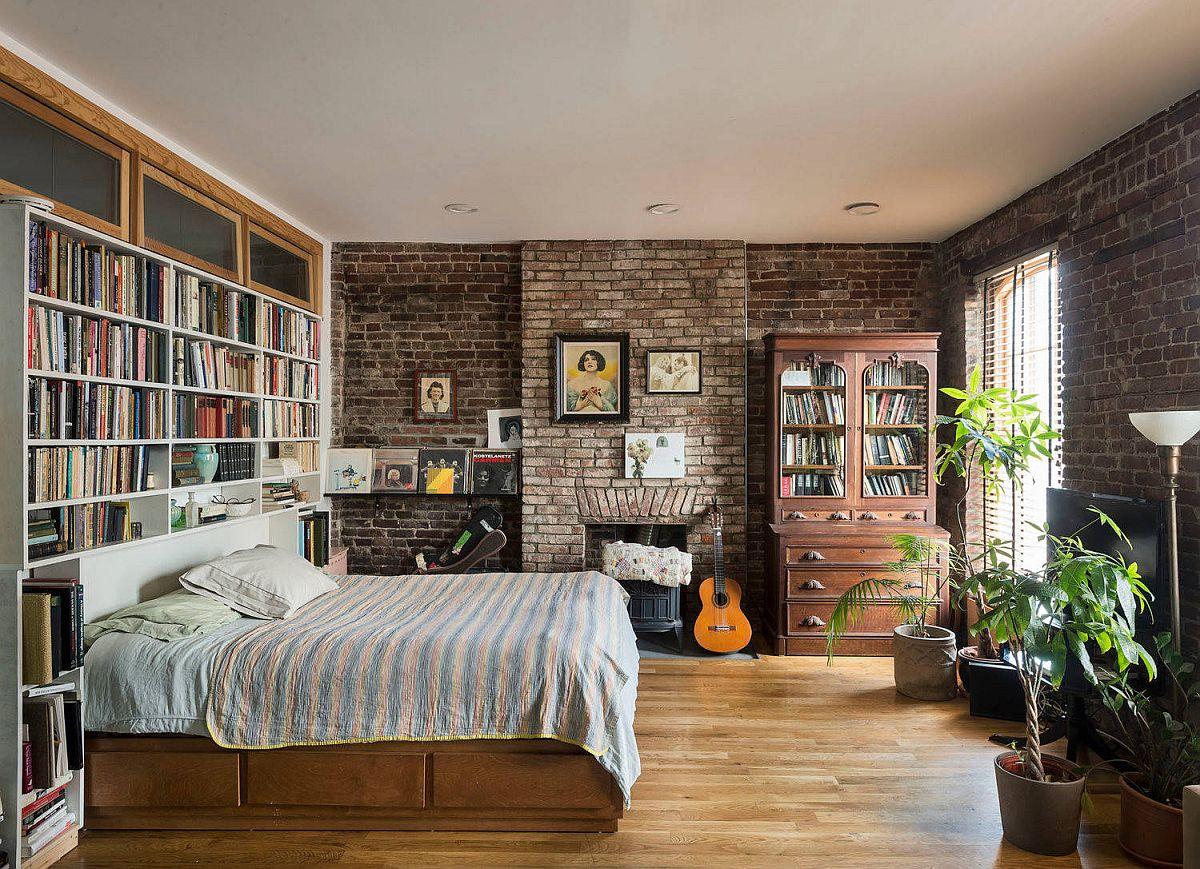 Giá sách lớn cho phòng ngủ công nghiệp hiện đại với bức tường gạch và một chiếc giường êm ái
