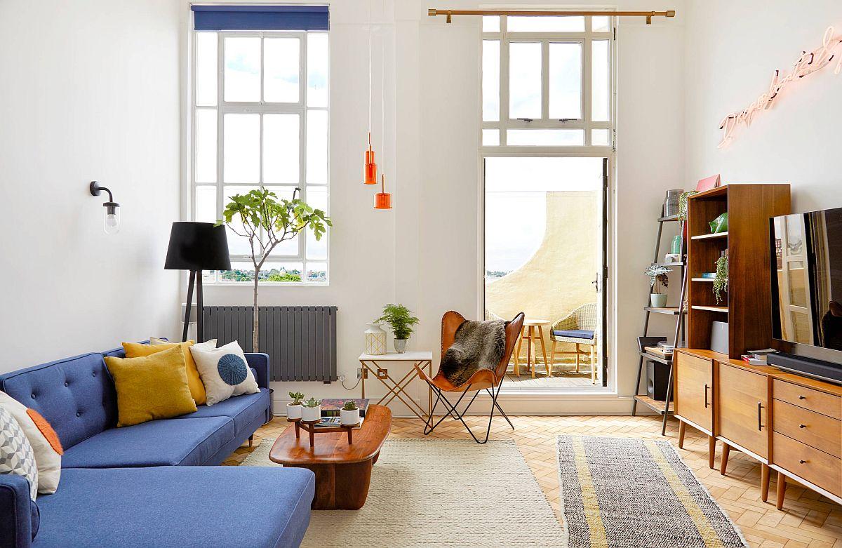 Phòng khách hiện đại giữa trung niên thông minh với đi văng màu xanh lam và gối nhấn màu vàng