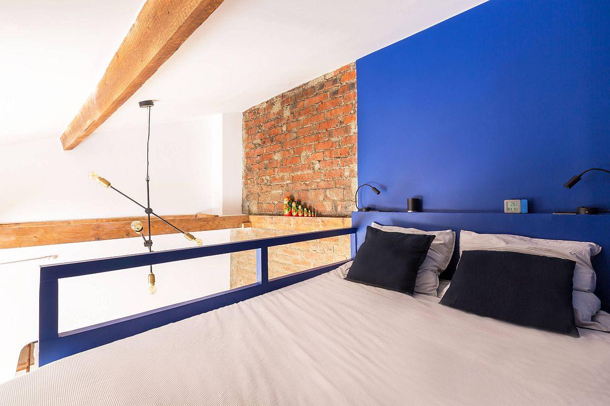 Phòng ngủ công nghiệp nhỏ nhắn với bức tường nổi bật màu xanh lam và thiết kế siêu phong cách