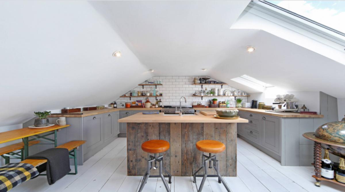 Kiến trúc sư đã tạo ra sự yên bình cho căn bếp bằng việc sử dụng gam màu trắng. Nhưng bí quyết để làm cho căn bếp áp mái trở nên ấm áp chính là chỉ sử dụng màu trắng ở xung quanh, còn ở trung tâm, mặt ghế băng, mặt bàn bếp, quầy bếp được sử dụng màu vàng, màu gỗ tự nhiên, kết hợp với ghế xoay với đêm da và gỗ lát sàn tấm mộc.