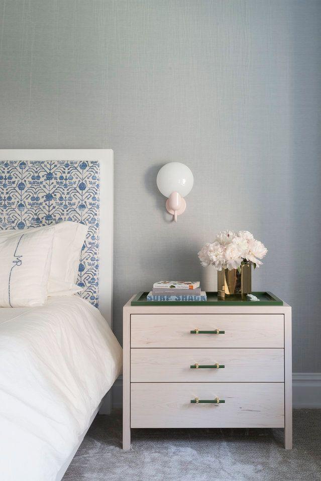 Một chiếc đèn treo tường màu hồng baby và đầu giường bọc nệm màu xanh lam tạo thêm chút ngọt ngào cho các yếu tố màu xanh lá cây và xám xuyên suốt.