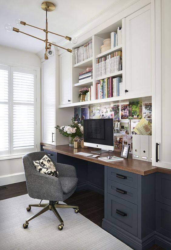 tủ bếp hai tông màu, bàn làm việc với mặt bàn bằng gỗ thịt, một chiếc ghế màu xám và một chiếc đèn chùm cổ điển