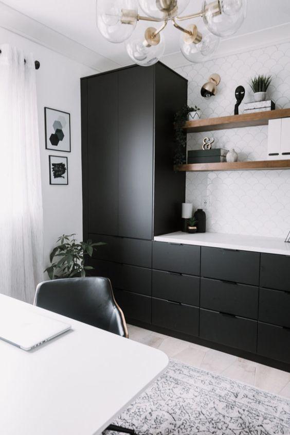 Không gian làm việc tại nhà hiện đại với tủ đen kiểu dáng đẹp và gạch nền trắng, kệ nổi và bàn làm việc màu trắng cộng với đèn chùm cổ điển