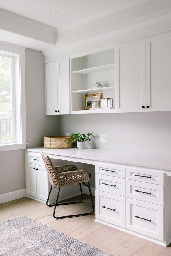 Không gian với phong cách trung tính hiện đại tại nhà với tủ kiểu shaker màu trắng, bàn làm việc có nhiều đồ, ghế mây và một số cây