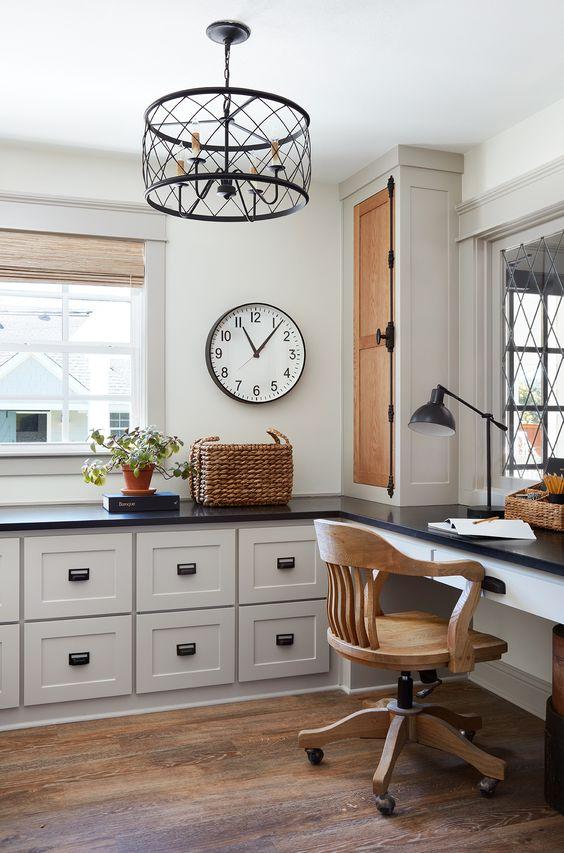 Không gian đầy phong cách được trang bị đồ gỗ nhà bếp xinh xắn và bàn làm việc, ghế gỗ, đèn chùm kim loại và một cái giỏ
