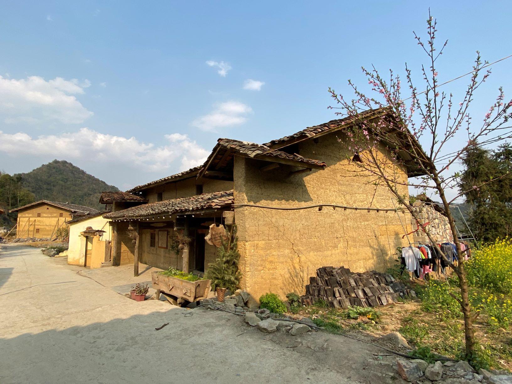 Nhà trình tường với bức tường đất vàng thổ và mái ngói âm dương thẫm màu thời gian