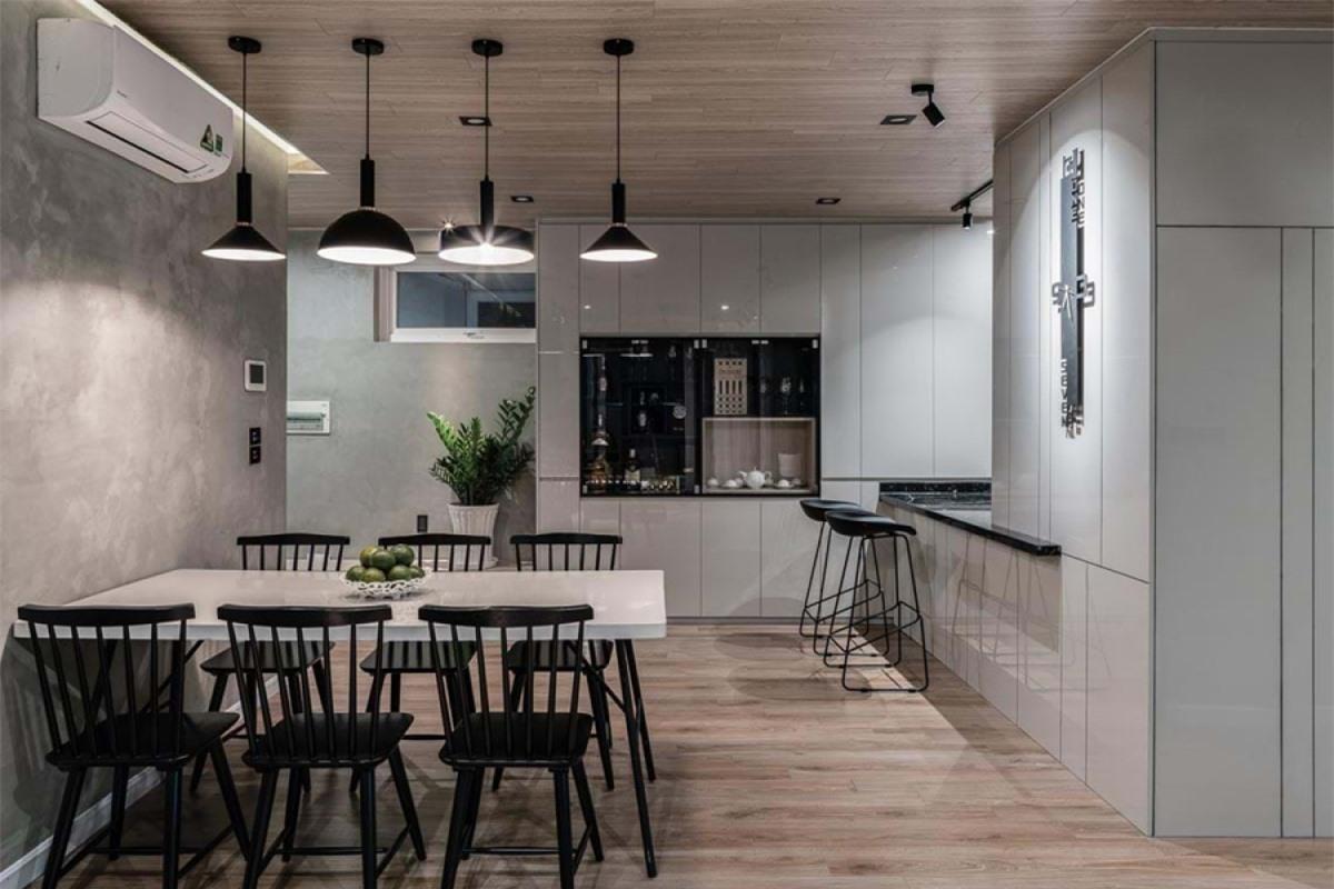 Khu vực bếp và phòng ăn nằm ở phía sâu, thiếu ánh sáng tự nhiên nên được ưu tiên nhiều màu trắng hơn ở hệ tủ bếp. Chất liệu gỗ ở trần và sàn màu nâu và tường màu xám vẫn là màu chủ đạo.